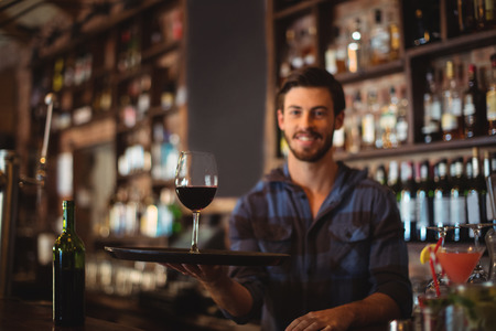 hotel staff: Portrait of bar tender holding a tray with glass of red wine at bar counter