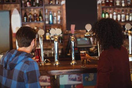 beer pump: Friends having beer at bar counter in pub