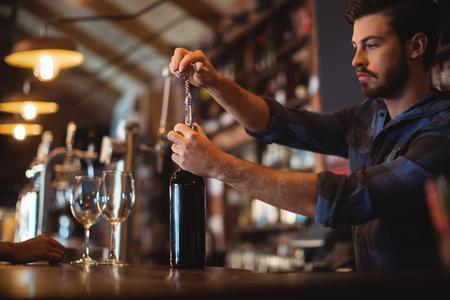 Hombre bar tender abriendo una botella de vino en la barra de bar Foto de archivo - 77402646