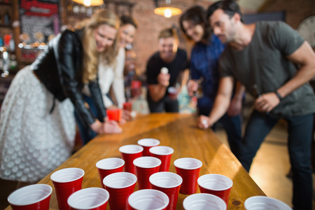 Friends enjoying beer pong game on table in bar Stockfoto