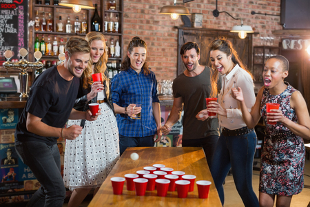 Friends cheering while man playing beer pong on table in bar Stock Photo - 77424844