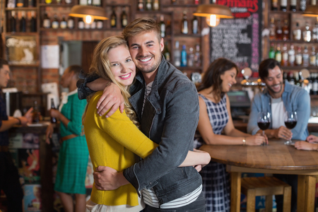 Portrait of smiling young couple hugging in pub Stock Photo