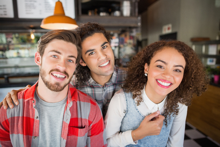 Portrait of smiling young friends in restaurant Stock Photo