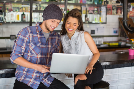 Happy friends using laptop while sitting by counter in restaurant Stock Photo