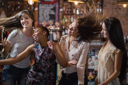 Carefree female friends dancing at pub