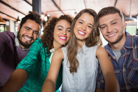 Portrait of cheerful friends in restaurant