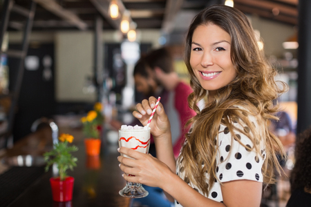 Portrait of woman holding drink in restaurant