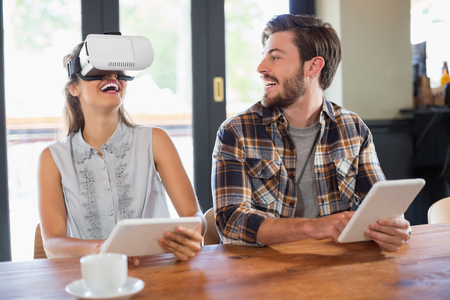 Young man looking at female friend wearing virtual reality glasses in cafe Stock Photo