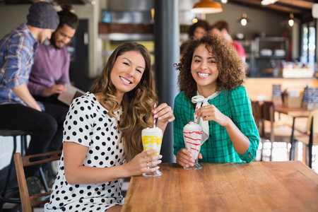 Portrait of happy female friends holding smoothies at table in restaurant