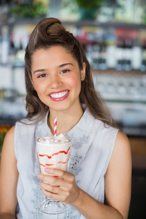 Portrait of beautiful young woman drinking smoothie at restaurant