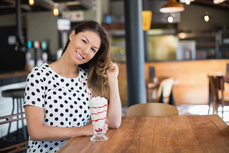 Portrait of young woman sitting by drink on table in restaurant