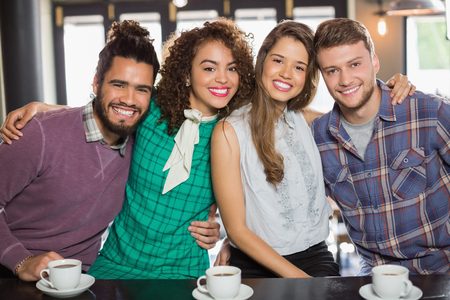 Portrait of cheerful friends sitting in cafe