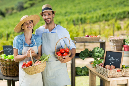 Portrait of smiling couple holding fresh vegetables in baskets at farm