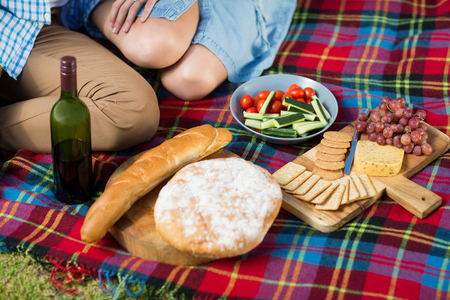 High angle view of wine bottle and food by couple on picnic blanket