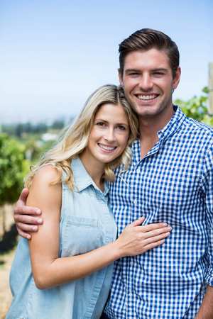 Portrait of happy couple embracing at vineyard during sunny day