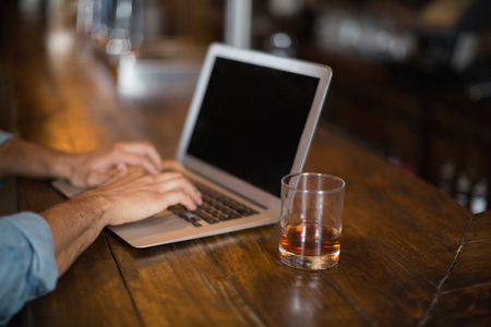 Cropped hands of man using laptop by beer glass at pub Stock Photo