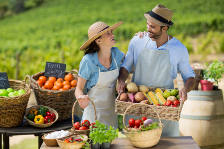 Happy couple standing by fresh fruits and vegetables at farm