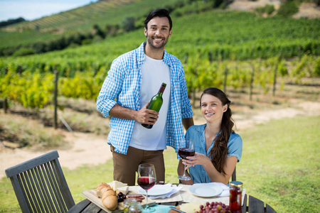 Portrait of smiling couple holding red wine bottle and glass with vineyard in background