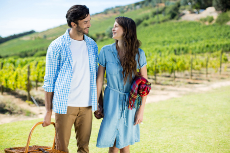 Happy couple looking at each other with holding picnic blanket and basket with vineyard in background