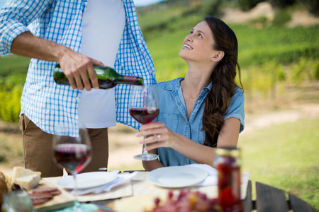 Smiling woman looking at man pouring red wine in glass at table