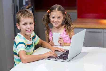 Portrait of smiling siblings using laptop in kitchen at home