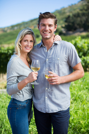 Portrait of happy young couple holding wineglasses at vineyard