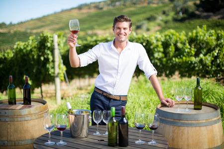 畑でグラスとボトルをテーブルの上で立ちながらワイングラスを持って若い男の肖像