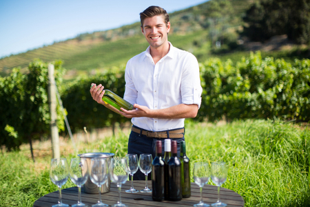 Portrait of young man holding wine bottle while standing by wineglasses and bottles on table at vineyard Stock Photo