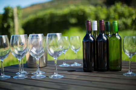 Wineglasses and bottles on wooden table
