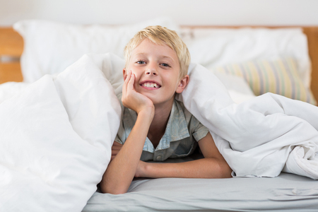 bed sheet: Portrait of smiling boy lying under bed sheet in bedroom at home