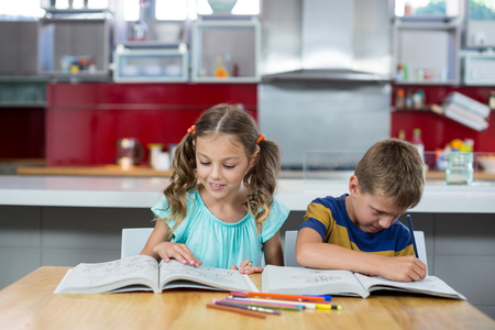 Siblings doing homework in kitchen at home