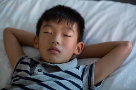 overtired: Boy sleeping on bed in bedroom at home Stock Photo