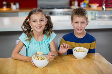 niños desayunando: Portrait of smiling sibling having breakfast cereal in kitchen at home