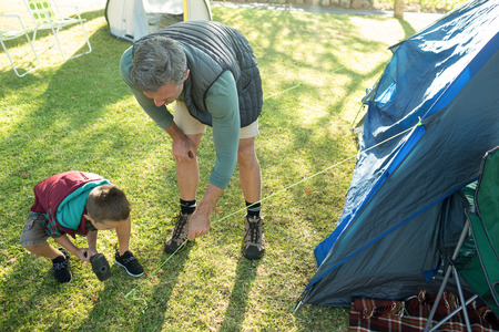 campsite: Father and son setting up the tent at campsite
