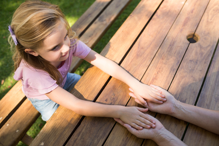 Mother and daughter holding hands on picnic table in park