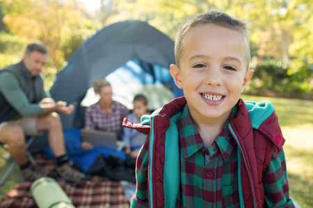 Boy smiling at camera while family sitting at tent in background on a sunny day Stock Photo