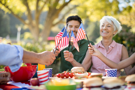 Happy family holding american flags while having meal in the park