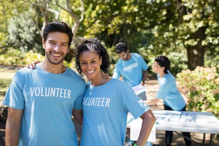 Portrait of smiling volunteers standing in the park Foto de archivo