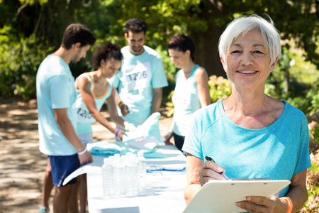 Coach smiling while athletes registering for marathon in the park Stock Photo
