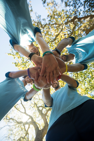 Low angle view of volunteers forming a hand stack in the park