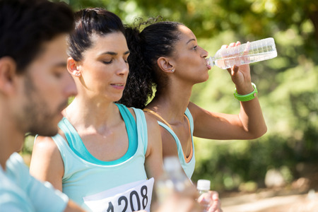 Marathon athletes having water in the park Stock Photo