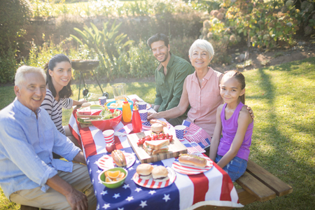 Happy family having meal in the park on a sunny day Stock Photo