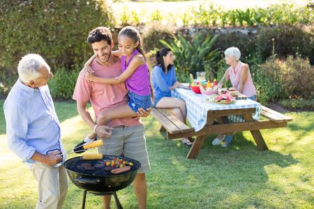 Glückliches Mädchen, Vater und Großvater, die Grill im Park vorbereitet Standard-Bild - 77600755