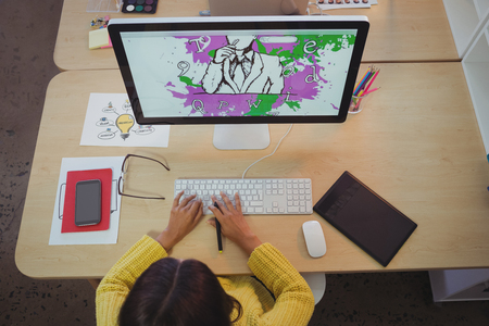 Overhead view of female graphic designer working in creative office