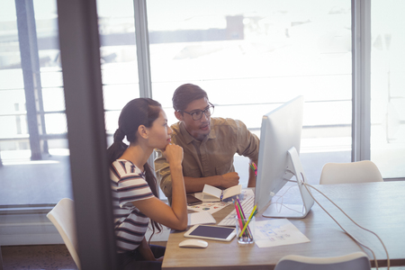 Businessman and businesswoman discussing over computer in office
