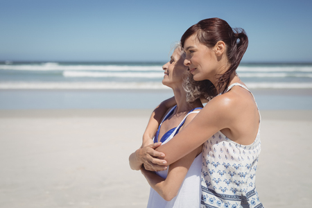 Side view of happy woman embracing her mother at beach during sunny day