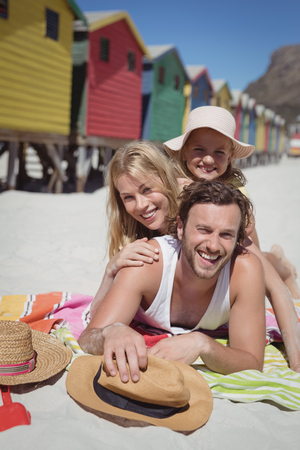 Portrait of happy family lying together on blanket at beach during sunny day