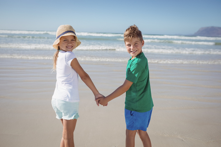 Portrait of siblings holding hands on shore at beach during sunny day