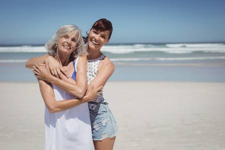 Portrait of happy woman with her mother standing at beach during sunny day Reklamní fotografie