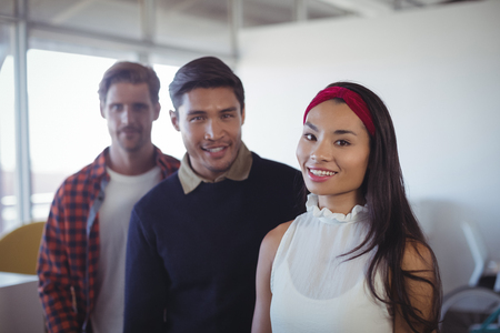 Portrait of young business colleagues standing together at office Stock Photo
